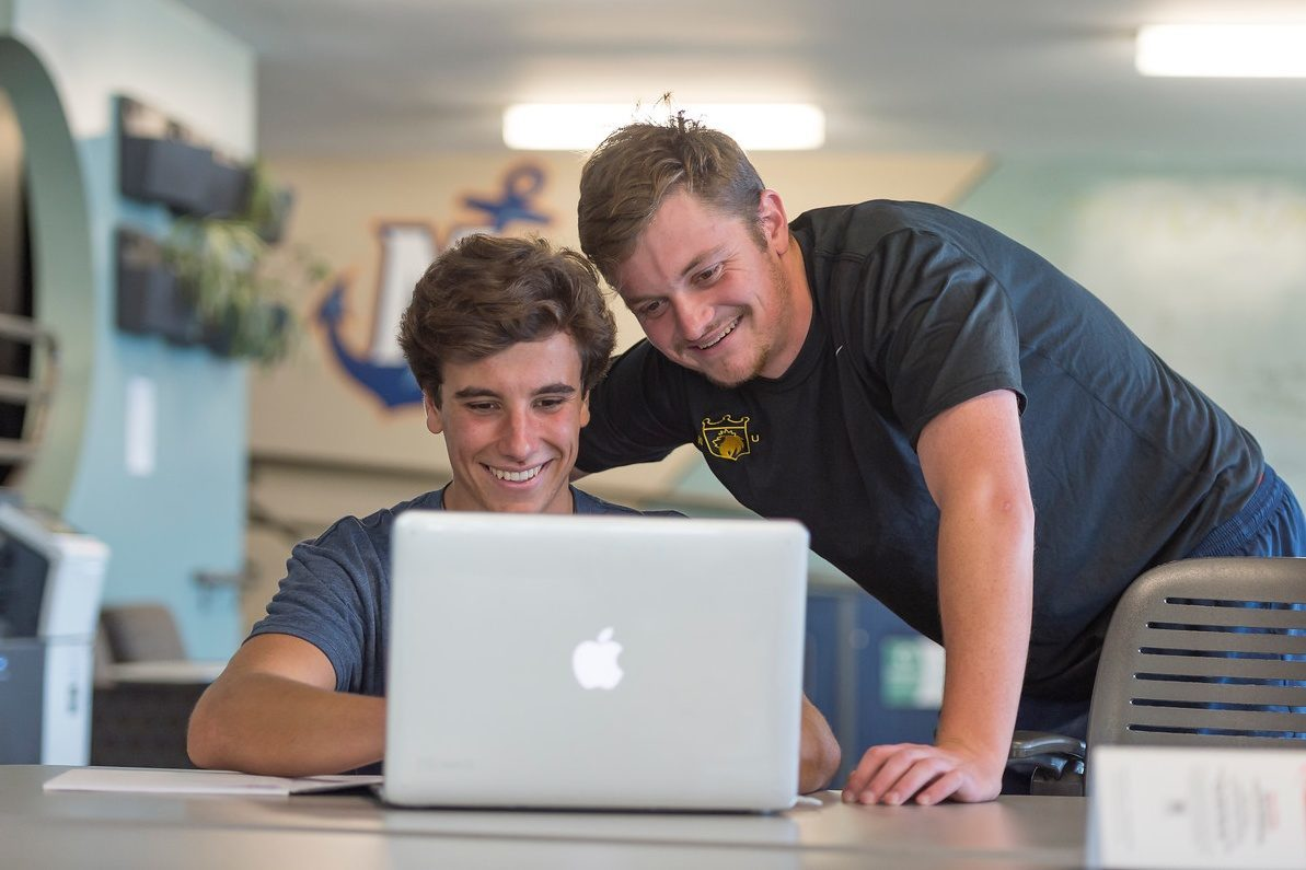 2 male students looking at laptop