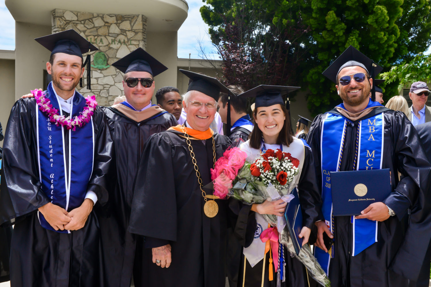 students and university president in cap and gown