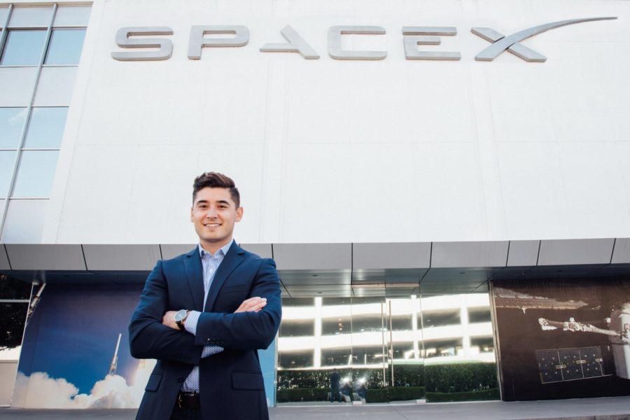 student standing with arms crossed in front of space x building