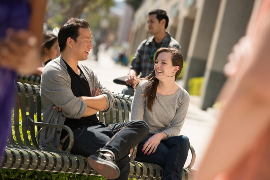 students sitting on a bench on a sunny day