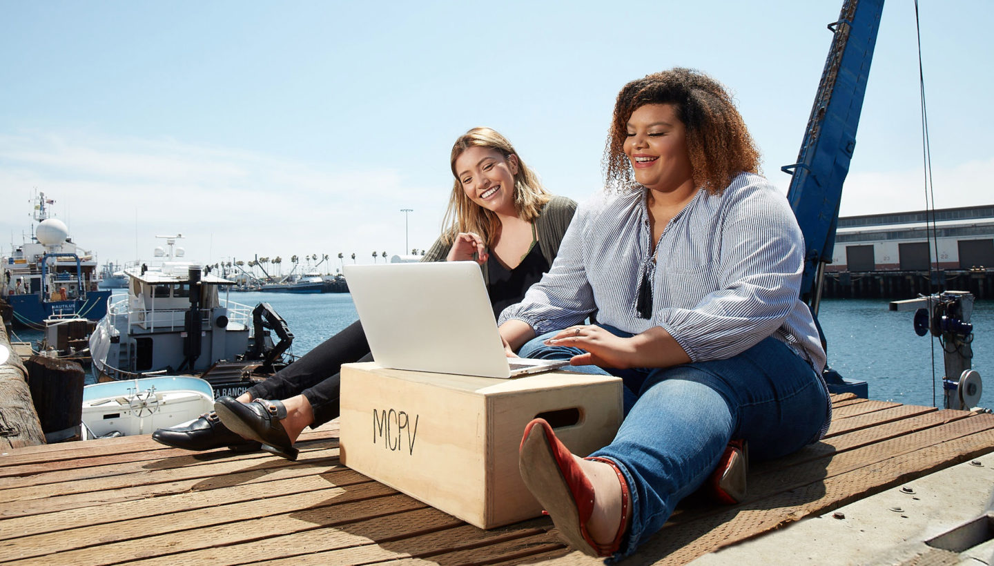 Students at laptop with LA port in background