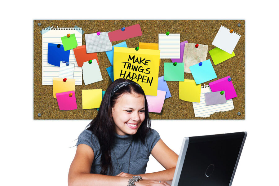 student at computer with bulletin board behind her