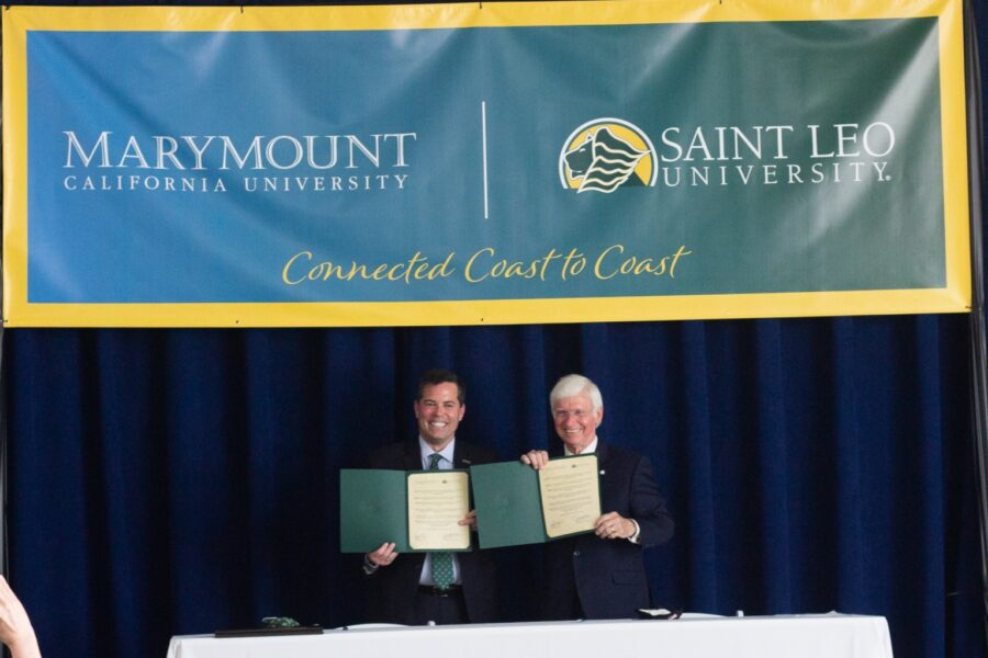 Saint Leo President Jeffrey Senese (left) and MCU President Brian Marcotte sign the agreement between the two universities